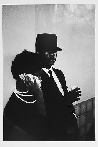 Woman, handkerchief to face, man looking at me mid 1950s Gelatin Silver Print