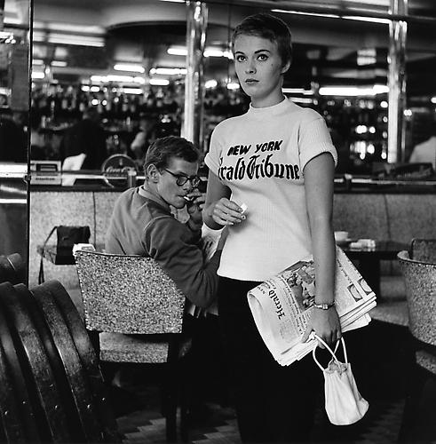 Jean Seberg walking out of a cafe on the Champs Elysees to join the team shooting (A Bout De Souffle) 1959  gelatin silver print