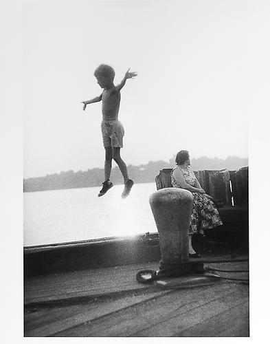 Boy jumping in mid-air on dock mid 1950s Gelatin Silver Print
