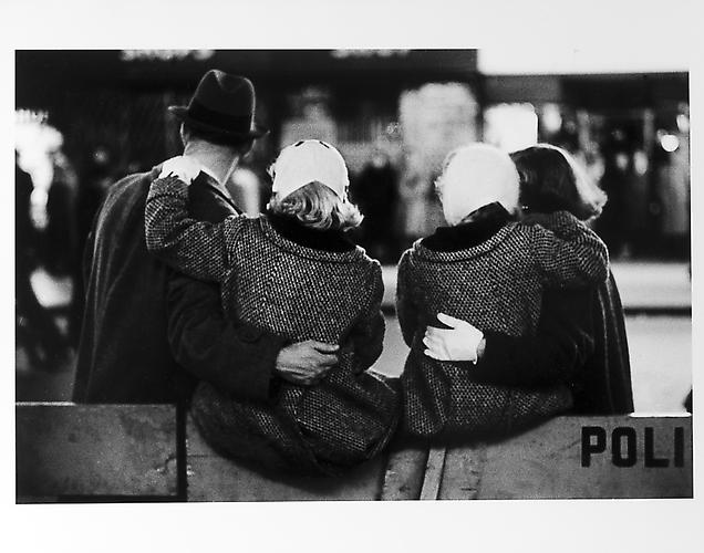 Children sitting on barricade with parents, New Year's Eve mid 1950s Gelatin Silver Print