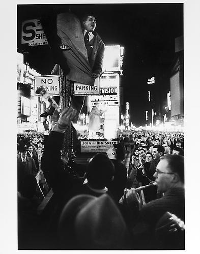 Man climbing on a light pole, New Year's Eve mid 1950s Gelatin Silver Print
