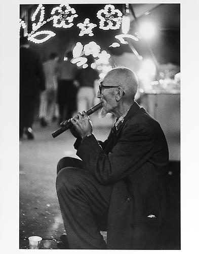 Old man with flute at San Gennarro Festival  mid 1950s Gelatin Silver Print