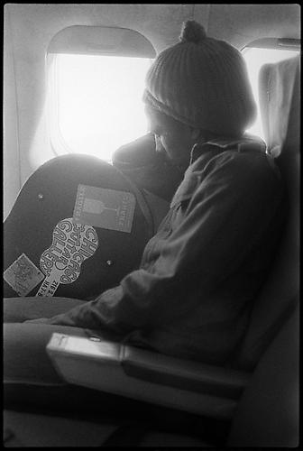 Bob sleeping on the plane, leaning on guitar case Silver Gelatin