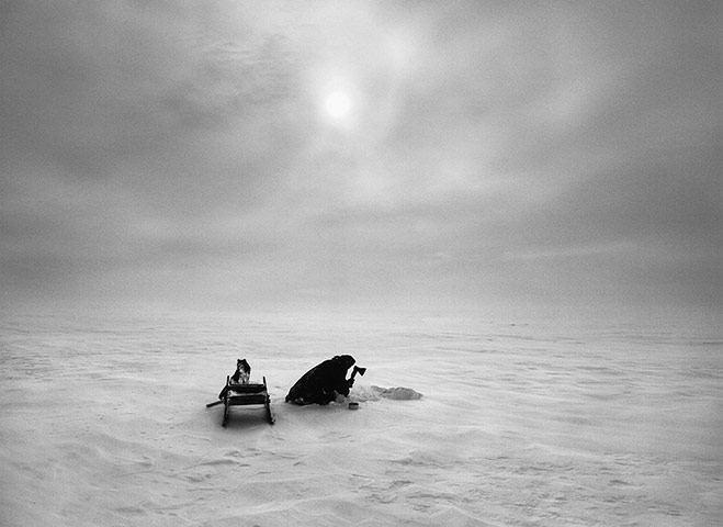 Nenets Nomads (cutting ice), Siberia, Russia.  2011 Gelatin silver print  Ice cut out of a frozen lake is melted and the water used for cooking and drinking. The Nenets struggle to find enough fresh water and use it very sparingly, for instance rarely washing themselves.
