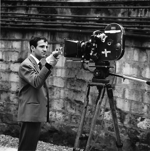 Francois Truffaut, cigarette in his mouth, standing in front of an Éclair CAMEFLEX CM3 camera holding a hand puppet in front of the lens 1961 gelatin silver print
