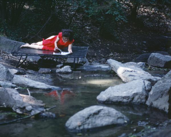 Rivers, First Draft: The Woman in Red, on a bed jutting into the water, skims an accordion-folded album of photos (1982/2015) Digital C-print from Kodachrome 35mm slides in 48 parts, 16h x 20w in (40.6h x 50.8w cm) Edition of 8 with 2 AP