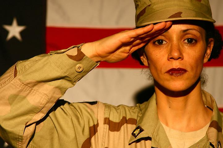A photo of a woman in khaki military fatigues giving a salute. The American flag is behind her.