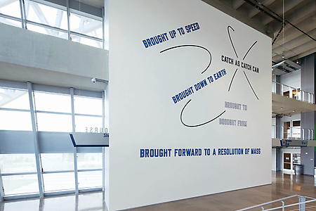 Lawrence Weiner <i>BROUGHT UP TO SPEED,</i> 2009 Vinyl decals on wall Dimensions variable Permanent installation Dallas Cowboys Stadium