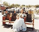 "Joel Sternfeld <i>Queen of the Prom, the Range Nightclub, Slab City, California, March 2005</i> from <i>Sweet Earth</i> Digital c-print Edition of 7 and 3 artist's proofs 26 1/2 x 33 1/4 (67.31 x 84.46 cm)  When Camp Dunlap, a World War II Marine training facility near Niland, California, was closed in 1946, all of the buildings were completely dismantled, leaving numerous cement foundation slabs in the desert.  Almost as soon as the government abandoned the site, ""snowbirds"" (campers from northern states in recreational vehicles) began to winter on the slabs, even though no running water, electricity or sewage facilities were available. Today at least five thousand snowbirds arrive each winter, and a few have become permanent year-round residents, despite summer temperatures that can reach 120 degrees. The snowbirds come with motor homes costing half a million dollars and they come with tents.  Over the years, a true self-governing community has arisen, including a mayor, the Slab City Christian Church (in a trailer), the Lizard Tree Library (used paperbacks on an honor system), the Gopher Flats Country Club (gravel greens), the Oasis Social Club  (combination meeting space/junkyard), a CB radio station (one half hour of purely local news, nightly at six p.m.) and the Range, an outdoor nightclub built by ""Builder Bill,"" complete with stage, lighting, bar, communal outhouse and several rows of salvaged airliner seats. The Range takes its name from an active bombing range located a few miles away, which makes the sight and sound of F-16 sorties a part of life at the Slabs.  Moira, the Queen of the 2005 Prom at the Range, never got to go to her high school prom."