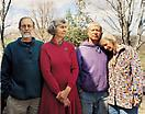 "Joel Sternfeld <i>Andy Wilson, Evelyn Edson, Tom and Ruth Klippstein at Springtree Commune, Scottsville, Virginia, April 2005</i> from <i>Sweet Earth</i> Digital c-print Edition of 7 and 3 artist's proofs 26 1/2 x 33 1/4 (67.31 x 84.46 cm)  The eight founders of Springtree first met at a Twin Oaks community conference in 1971. They all had children and wanted to build a community centered around them. By pooling their resources, they were able to purchase one hundred acres along the Hardnose River in Virginia, naming their new home for the old poplar tree that stood at the head of a clear spring. Each year, the founding of the community is celebrated there.  At its peak, Springtree was home to fifteen adults and fifteen children. It was, and still is, a close-knit intentional community in which ownership of land, homes and income is shared equally—a single checkbook still serves all. There is no leader or hierarchy. As a group they have never had an ambition for larger social change or commercial success, focusing instead on living well together (some might say their way of life is social change). Home schooling was a key element, and each child had an adult read with him or her nightly.  Not only did the group initially live together in the large house that they built, they also vacationed together. They drove by school bus to the outer banks of North Carolina and camped. The annual trip to the beach now functions as a reunion for Springtree members, their children and grandchildren.  Time and change have slowly eroded the community's numbers—two couples and an occasional intern live at Springtree today, sharing meals and conversation, and working in the garden and orchards together. An extensive calendar of visits from and to the world at large often interrupts the routine of farm work.  Asked what she was thinking when this group portrait was made, Ruth Klippstein responded, ""Though I'm not very smiley in the picture, I imagine I was thinking the main thoughts that make me happy: this is my place, these are my people. It's great to be rooted."""