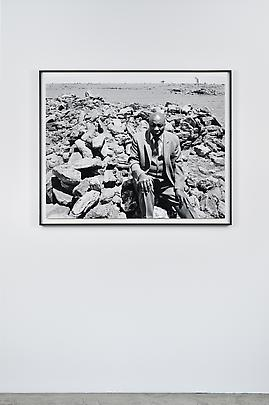 """<i>Luke Kgatitsoe in his house, bulldozed in February 1984 by the government after the forced removal of the people of Magopa, a black-owned farm, which had been declared a """"black spot,"""" Ventersdorp district, Transvaal. 21 October 1986</i> Image"""