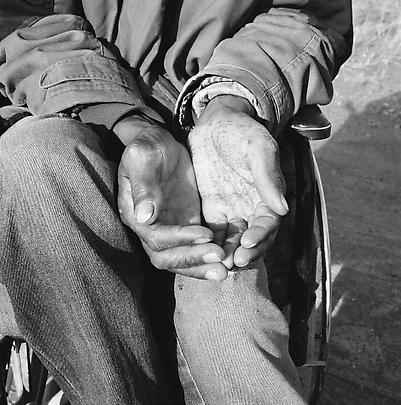 Particulars <b>Crippled by a stray bullet from an argument in which he had no part, a former gold-miner sits in a wheelchair and begs at a crossroad on the Johannesburg-Cape Town highway, while pursuing winning numbers for the national lottery.  Springfontein</b>. 7 August, 2003 Image