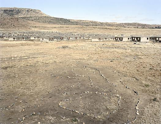 <b>Remains of households in a children's game called onopopi, and the shells of incomplete houses in a housing scheme that stalled. Kwezinaledi, Lady Grey, Eastern Cape</b>. 5 August 2006 Image