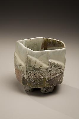 Tamba ware glazed footed teabowl with faceted carved exterior, 2007 Wood-fired stoneware with creamy ladle-poured ash and iron-oxide glazes  3 7/8 x 5 1/2 x 5 inches Inv# 5645