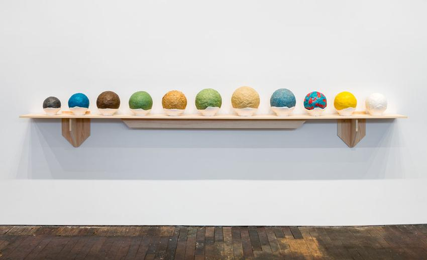 Circumstantial Balls<br />2003-2015<br />balled masking tape with acrylic paint, graphite, and colored pencil on plaster and cheese cloth base in 11 parts, wooden White Pine shelf<br />overall: 24 x 144 x 12 1/2 inches<br />  (61 x 365.8 x 31.8 cm)<br />PF3959<br />
