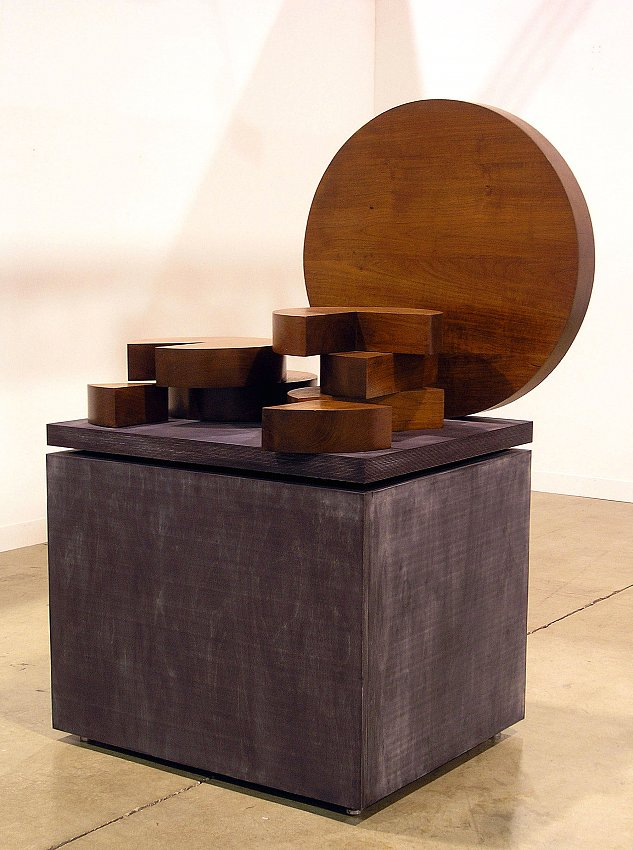 MICHAEL HEIZER<br /><br /><i>Thailand</i><br />1977<br />teak wood sculpture in eight parts on anodyne-dyed plywood base by the artist<br />overall: 62 1/2 x 43 1/2 x 32 inches (157.4 x 109.2 x  81.2 cm)<br />largest element: 32 inches in diameter (81.2 cm)<br />