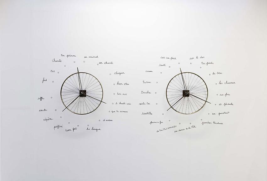 Robert Filliou<br />Danse-poème collectif<br />(à performer deux par deux, chacun(e) tournant<br />une roue)<br />[Replica of a 1962 performance]<br />1962<br />2 metal wheels and marker on wall<br />wheels: diameter 25 1/4 inches each<br />(64 cm each)<br />