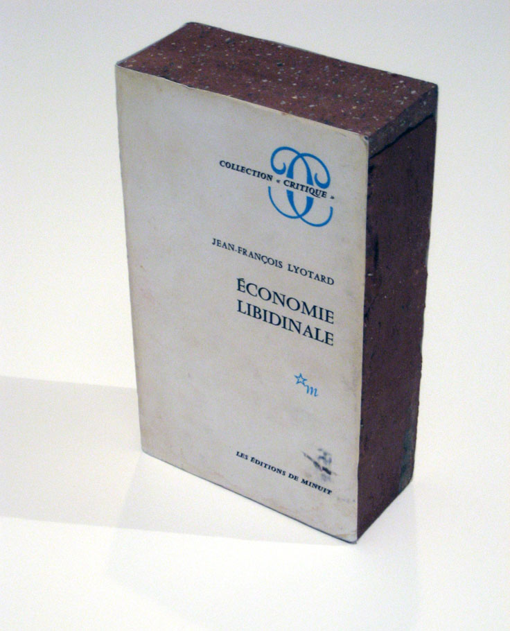 Claire Fontaine <i>Économie libidinale brickbat</i> 2010 Brick, brick fragments, digital archival print and elastic band 8 3/8 x 5 x 2 1/4 inches