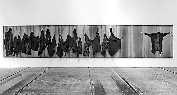 Untitled 2012 iron panel, iron hooks and overcoats 200 x 1080 x 9 cm exhibition view at Tramway, Glasgow 2012